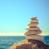 As pedras equilibram na praia, pilha sobre o mar azul Foto de Stock Royalty Free