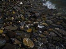As pedras molhadas do mar na costa são lavadas por uma água fotos de stock royalty free