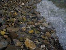 As pedras molhadas do mar na costa são lavadas por uma onda imagem de stock