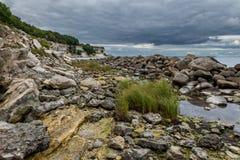 As pedras no primeiro plano da pedra calcária inclinam-se em Stevns, Dinamarca Imagem de Stock