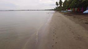 As pegadas, as bandeiras coloridas da bandeira e o parasol do guarda-chuva alinham no Sandy Beach vazio tropical filme