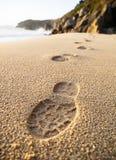 As pegadas detalham na areia da praia Imagens de Stock