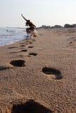 As pegadas na areia deixaram uma menina Imagem de Stock Royalty Free
