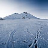 As pegadas na neve no pé de um pico de montanha montam Fotografia de Stock Royalty Free