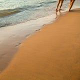 As pegadas na praia sairam atrás dos pares de povos que andam ao longo da praia da areia Fotografia de Stock Royalty Free