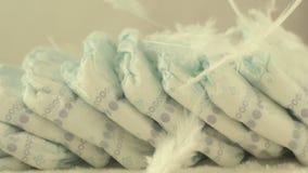 As penas delicadas brancas caem em tecidos do bebê, no conceito do conforto e na luminosidade, movimento lento filme