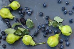 As peras e a ameixoeira-brava são ficadas situadas em um fundo escuro na ordem aleatória foto de stock
