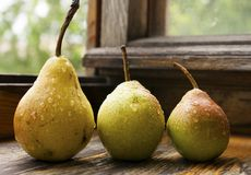 As peras maduras em uma tabela de madeira com água deixam cair Imagens de Stock