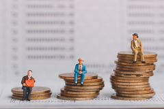 As pessoas adultas figuram o assento na pilha das moedas de prata na caderneta bancária do banco fotos de stock