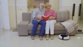 As pessoas adultas guardam o livro nas mãos e olham in camera de assento no sofá em casa vídeos de arquivo