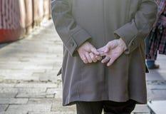 As pessoas idosas enrugaram as mãos guardadas behing sua parte traseira ao andar fotos de stock