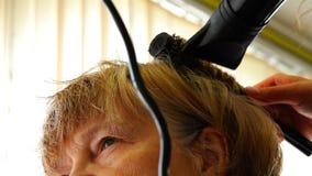 As pessoas idosas uma mulher são dadas um corte de cabelo em sua cabeça video estoque