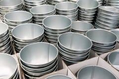 As pilhas da lata de prata buckets nas caixas onduladas brancas fotos de stock