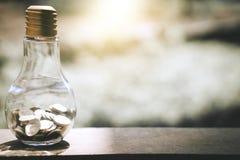 As pilhas da moeda no banco do vidro de garrafa para intensificam o negócio crescente imagens de stock