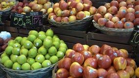 As pilhas de maçãs frescas saborosos maduras e de laranjas vermelhas e verdes nas cestas no mercado arquivam filme