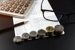 As pilhas de moeda e e de calculadora na operação bancária esclarecem o negócio Foto de Stock