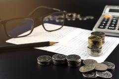 As pilhas de moeda e e de calculadora na operação bancária esclarecem o negócio Fotografia de Stock Royalty Free