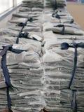 As pilhas de roupa embalaram em uns sacos de plástico prontos para ser enviado/distribuído fotos de stock royalty free