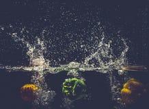 As pimentas de sino vermelhas amarelas verdes deixam cair na água com respingo Fotos de Stock