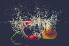 As pimentas de sino vermelhas amarelas verdes deixam cair na água com respingo Foto de Stock Royalty Free