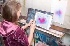 As pinturas do adolescente da menina com um aerógrafo coloriram brilhantemente imagens do inverno do Natal em um estúdio artístic Fotografia de Stock