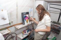 As pinturas do adolescente da menina com um aerógrafo coloriram brilhantemente imagens em um estúdio artístico - Rússia, Moscou - Fotografia de Stock