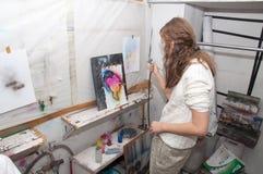 As pinturas do adolescente da menina com um aerógrafo coloriram brilhantemente imagens em um estúdio artístico - Rússia, Moscou - Imagem de Stock