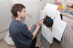 As pinturas do adolescente do menino com um aerógrafo coloriram brilhantemente imagens em um estúdio artístico - Rússia, Moscou - Foto de Stock