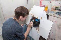 As pinturas do adolescente do menino com um aerógrafo coloriram brilhantemente imagens em um estúdio artístico - Rússia, Moscou - Imagem de Stock Royalty Free