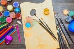 As pinturas do guache e de óleo, escovas para pintar, escrevem o pastel na tabela de madeira escura Vista superior Imagens de Stock