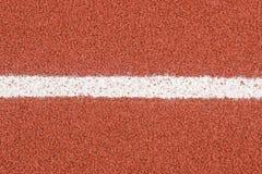 As pistas de borracha da pista de atletismo cobrem a textura com a linha para o fundo imagens de stock royalty free
