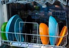 As placas coloridas limpas estão na máquina da máquina de lavar louça fotos de stock