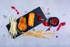 As placas de queijo serviram com varas e doce de pão em uma placa da ardósia imagem de stock royalty free
