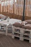 As poltronas com coxins fizeram o ‹do †do ‹do †com madeira em um café exterior Fotos de Stock Royalty Free