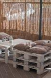 As poltronas com coxins fizeram o ‹do †do ‹do †com madeira em um café exterior Fotografia de Stock Royalty Free