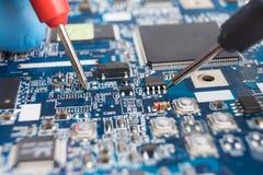 As pontas de prova do verificador tocam nos terminais da microplaqueta Reparo do computador macrophotography imagem de stock