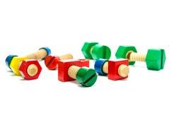 As porcas de madeira coloridas - e - os parafusos brincam Imagem de Stock Royalty Free