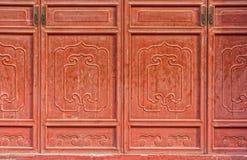 As portas cinzeladas de madeira chinesas vermelhas antigas do templo Imagem de Stock