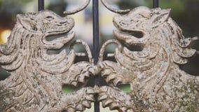 As portas do ferro da forja do palácio luxary real velho com os dois leões forjados dourados, câmera são lentamente gerenciem e d vídeos de arquivo