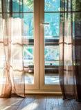 As portas francesas abrem em um balcão com uma vista de árvores verdes frondosas nave Relaxe o conceito vocations fotografia de stock royalty free