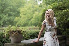 As poses louras novas impressionantes da mulher na cópia floral branca vestem-se Fotos de Stock Royalty Free