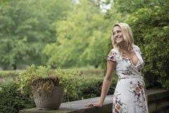 As poses louras novas impressionantes da mulher na cópia floral branca vestem-se Imagens de Stock Royalty Free