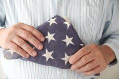 As posses do homem dobraram a bandeira americana Fotos de Stock