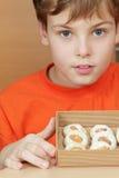 As posses do menino abrem a caixa de cartão ondulado com biscoitos Fotos de Stock Royalty Free