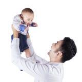 As posses felizes do paizinho e levantam acima seu bebê Imagem de Stock