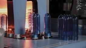 As pré-formas do ANIMAL DE ESTIMAÇÃO movem-se na linha do forno do aquecimento na velocidade rápida O plástico engarrafa a produç filme