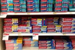 As prateleiras de Colgate marcam o dentífrico em uma loja Imagens de Stock