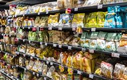 As prateleiras e o shelving com os produtos das bebidas e dos bens no supermercado SPAR fotografia de stock