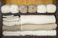 As prateleiras encheram-se por bolas das lãs, agulhas de confecção de malhas, telas de lã prontas Imagem de Stock