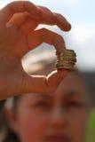 As preensões da menina empilharam moedas britânicas pela libra fotografia de stock